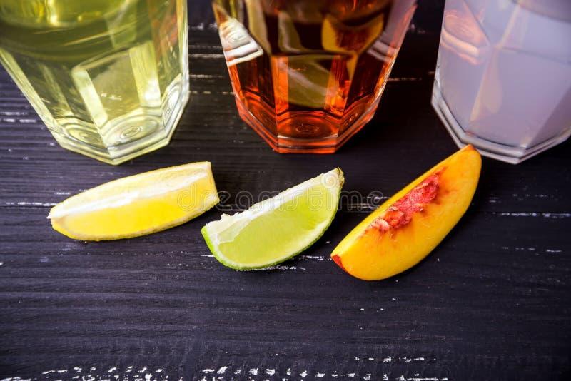 Draufsicht von drei Scheiben der verschiedenen Frucht und der glasess mit coctails auf einem Hintergrund In einem dunklen Holztis lizenzfreies stockfoto