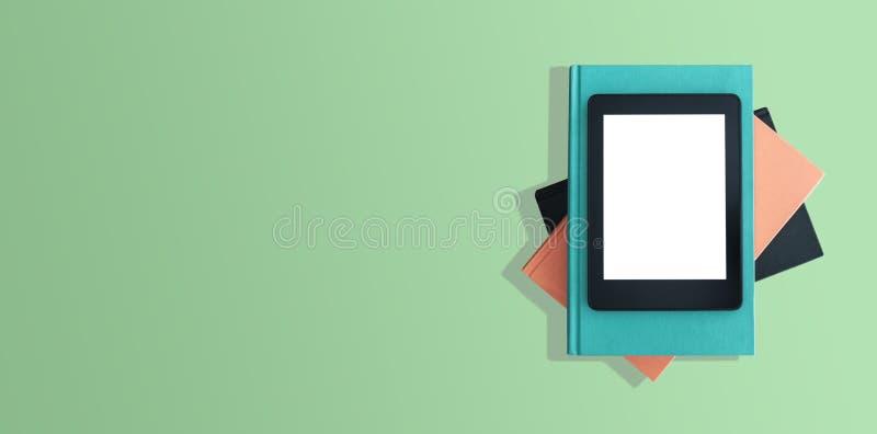 Draufsicht von eBook Leser auf Stapel Büchern auf dem grünen Desktop stockfotos
