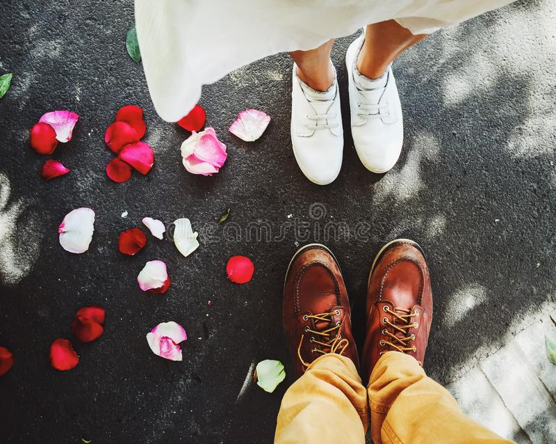 Draufsicht von Füßen eines jungen Paares mit wenigem schönem rotem rosafarbenem Blumenblatt aus den Grund lizenzfreies stockbild