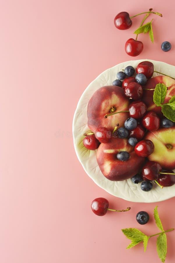 Draufsicht von Früchten eines frischen Sommers - Kirsche, Pfirsiche, Blaubeeren Rosa Hintergrund stockfoto
