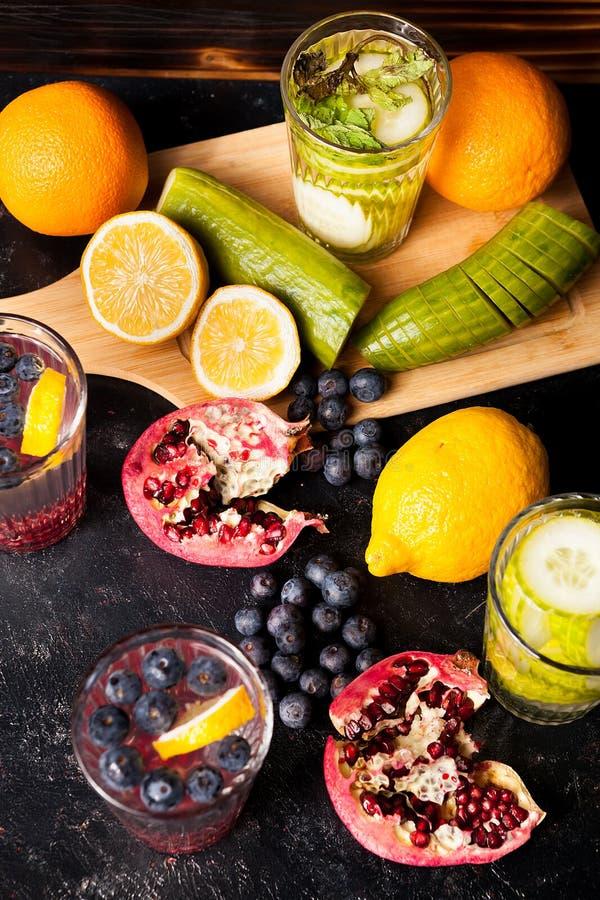 Draufsicht von Früchten, Gemüse und Beeren nahe bei Gläsern mit Detox wässern lizenzfreie stockbilder