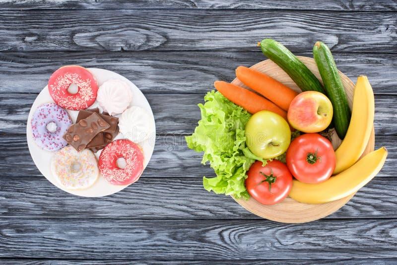 Draufsicht von frischen Früchten mit Gemüse und Bonbons auf Holztisch lizenzfreie stockfotos