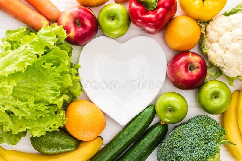 Draufsicht von frischen Früchten mit Gemüse und leerem Herzformblech auf hölzernem lizenzfreies stockfoto