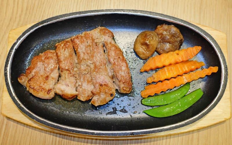 Draufsicht von gegrillten Rindfleischsteaks diente mit Gemüse auf hölzernem Brett lizenzfreie stockfotografie