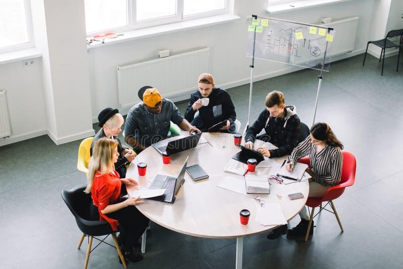 Draufsicht von gemischtrassigen jungen kreativen Leuten im modernen B?ro Gruppe junge Geschäftsleute arbeiten zusammen mit stockfotos