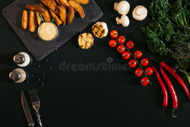 Draufsicht von geschmackvollen Ofenkartoffeln mit Soße, Gewürzen und Gemüse auf Schwarzem stockbilder
