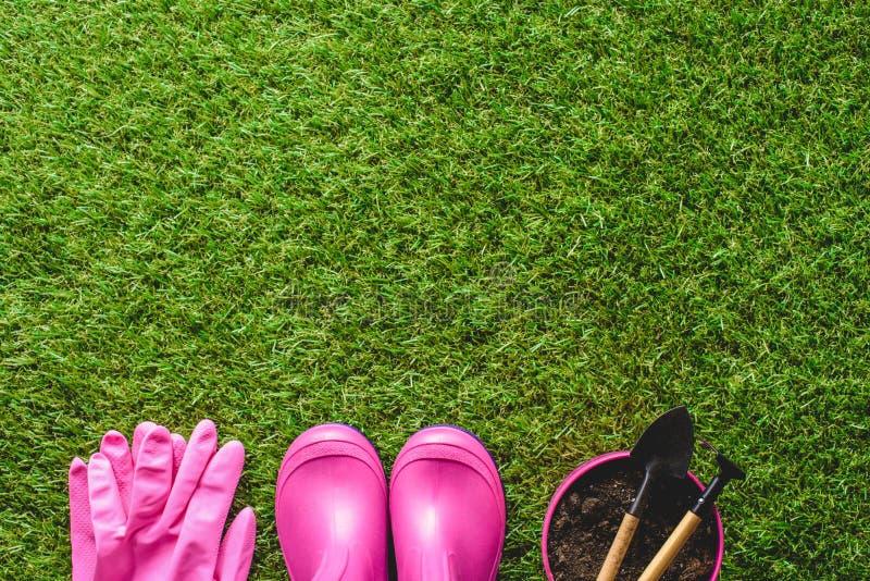 Draufsicht von Gummistiefeln, Schutzhandschuhe, Blumentopf mit Gartenarbeitwerkzeugen lizenzfreies stockbild