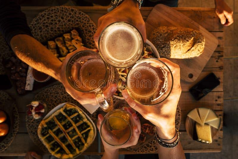 Draufsicht von Händen mit den Bieren, die zusammen, hölzerner zujubeln und haben Tabelle des Spaßes - Freunde am Abendessenfeiern lizenzfreie stockfotos