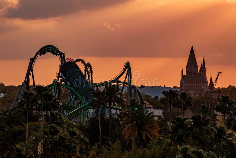 Draufsicht von Hogwarts-Schloss und von unglaublichen Rumpfachterbahn auf buntem Sonnenunterganghimmelhintergrund an Universal St stockbilder