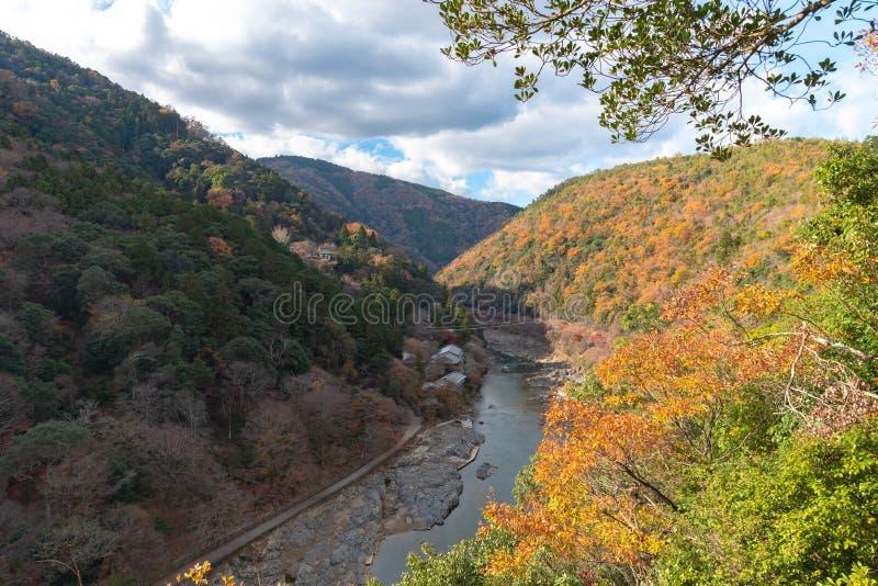 Draufsicht von Hozugawa-Fluss mit japanischem traditionellem Holzhaus, Boot und Herbstlaubfarben von Arashiyama-Standpunkt, Kam stockfoto