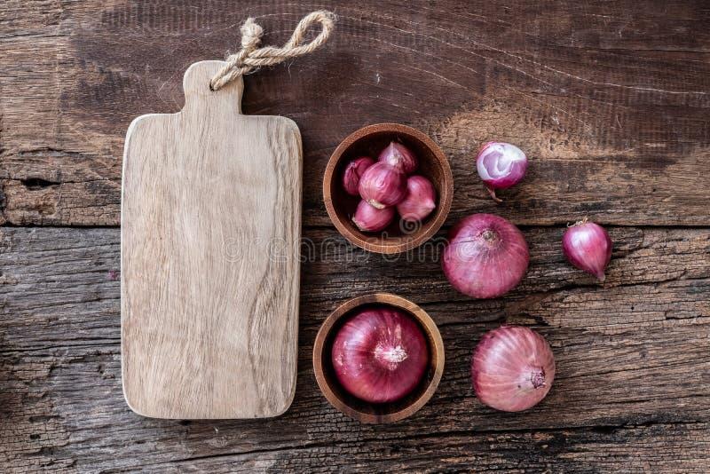 Draufsicht von Kräutergemüsebestandteilen, von frischer roter Zwiebel und von leerem hackendem Brett auf dem alten Holztisch, Vor lizenzfreie stockbilder