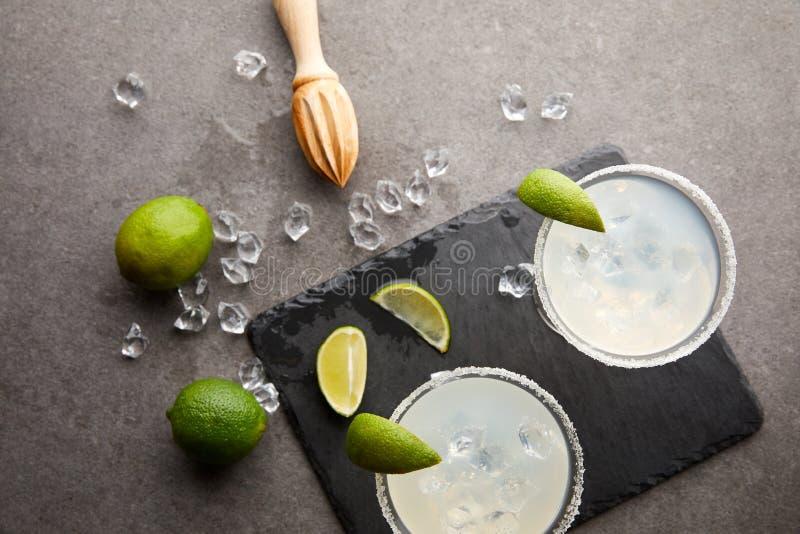Draufsicht von Margaritacocktails mit Stücken des Kalkes, der Eiswürfel und des hölzernen Quetschers auf grauer Tischplatte lizenzfreie stockbilder