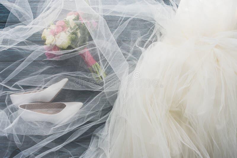 Draufsicht von Paaren von Schuhen, von Hochzeitskleid und von Blumenstrauß auf hölzerner Dunkelheit stockfoto