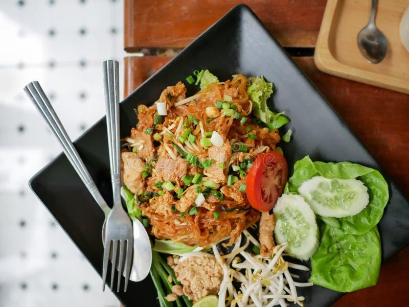 Draufsicht von Phadthai, populäre thailändische Nudellieblingsnahrung mit Gemüsebeilagen auf Schwarzblech lizenzfreie stockfotos