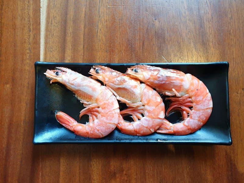 Draufsicht von rohen Garnelen im Schwarzblech auf Holztisch im Restaurant lizenzfreie stockfotos