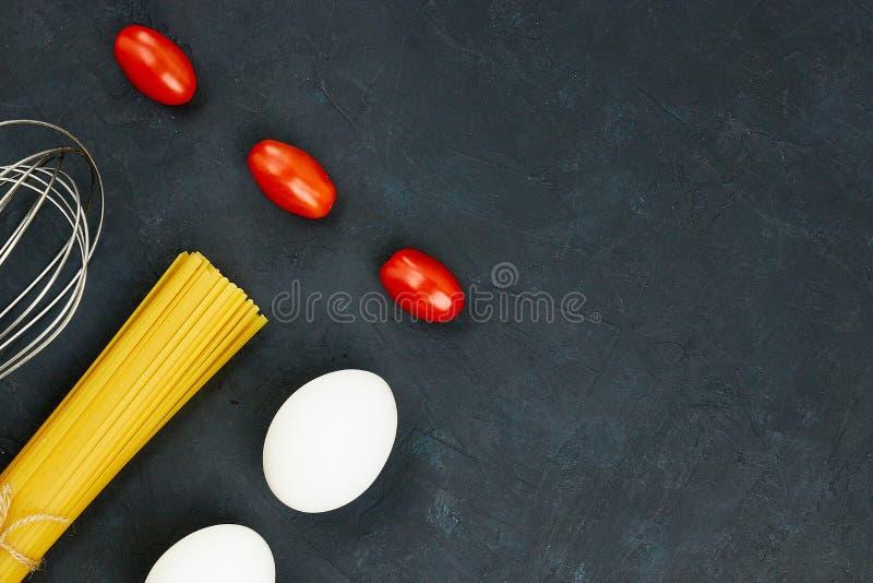 Draufsicht von rohen Teigwaren nahe bei Ei und Kirsche, frische Tomaten, auf schwarzem Hintergrund Kopieren Sie Platz stockbild