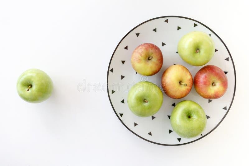Draufsicht von roten und grünen Äpfeln in der weißen Platte mit schwarzem Dreieckmuster und im grünen Apfel auf weißem Hintergrun stockfotografie
