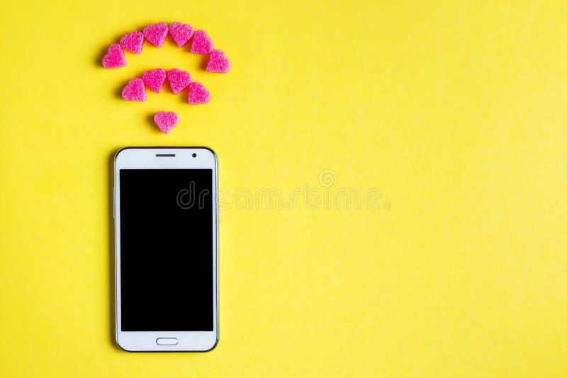 Draufsicht von Smartphone mit dem Symbol von Wi-FI von den dekorativen Herzen auf gelbem Papierhintergrund Internet-Technologie u stockbild