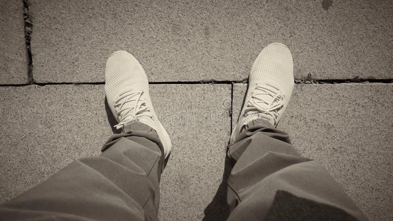 Draufsicht von Sport-Schuhen mit Steinstraßenhintergrund lizenzfreie stockbilder