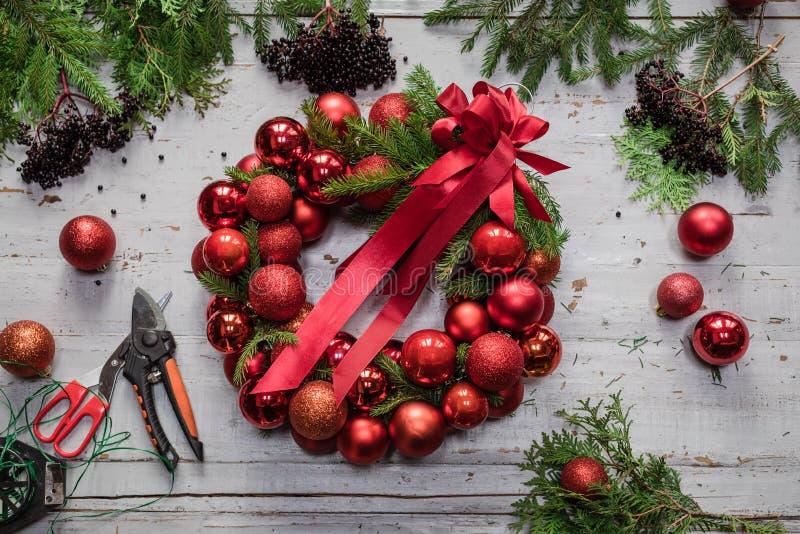 Draufsicht von Stadien der Herstellung des Weihnachtskranzes mit Tannenzweigen und dekorativen roten Bällen auf hölzerner rustika stockfoto