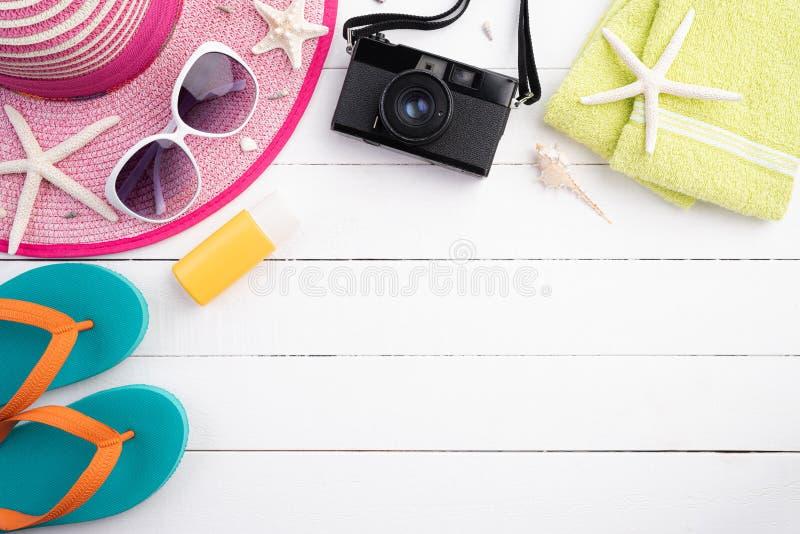 Draufsicht von Strandzusätzen einschließlich Flipflop, Starfish, Strandhut und Seeoberteil auf sandigem Strand und hölzernen Hint stockfotos