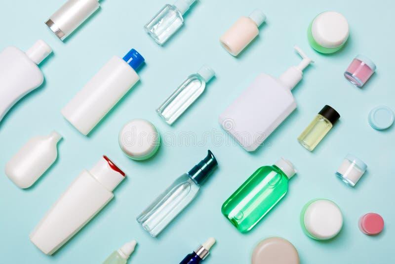 Draufsicht von unterschiedlichen kosmetischen Flaschen und von Behälter für Kosmetik auf blauem Hintergrund Flache Lagezusammense lizenzfreies stockfoto