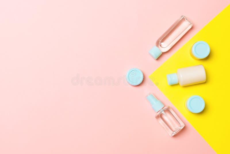 Draufsicht von unterschiedlichen kosmetischen Flaschen und von Behälter für Kosmetik auf Rosa und gelbem Hintergrund flache geleg stockfoto