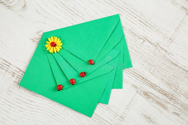 Draufsicht von vier grünen Umschlägen vom Recyclingpapier verziert mit Marienkäfern und gelben Blumenhandwerksverzierungen auf ei lizenzfreies stockbild