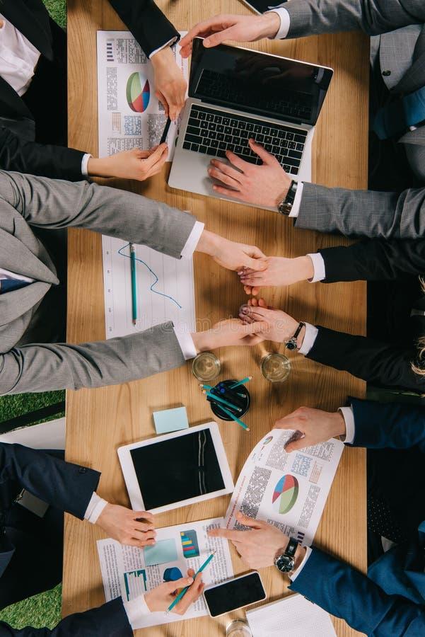 Draufsicht von zwei Geschäftskollegehändchenhalten während Mitarbeiter, die bei Tisch arbeiten lizenzfreie stockfotos