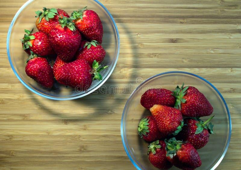 Draufsicht von zwei Klarglasschüsseln roten organischen Erdbeeren lizenzfreies stockbild