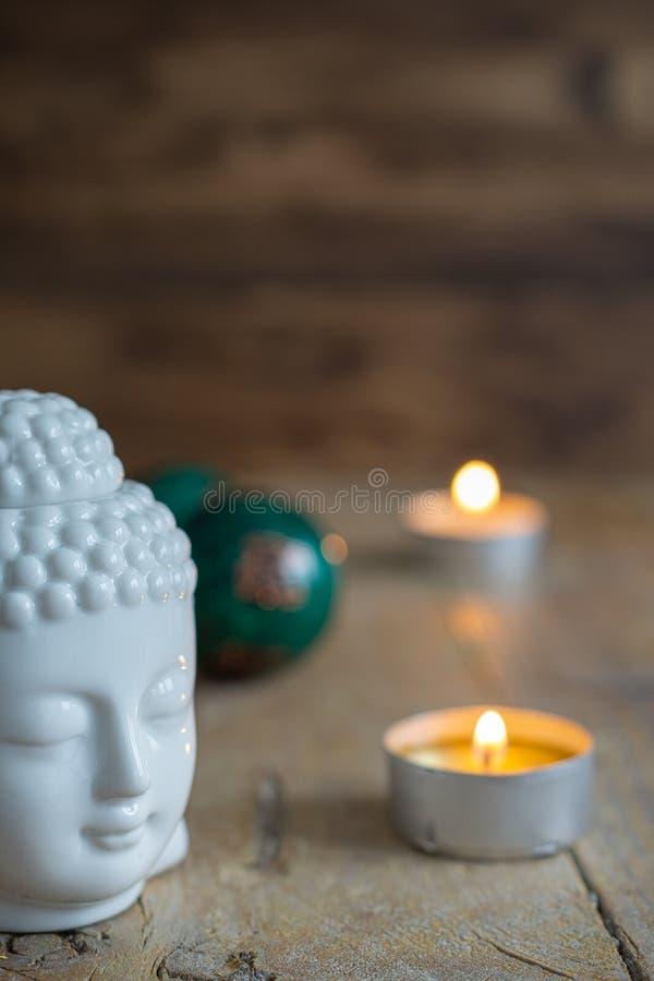 Draufsicht weißer Buddha-Zahl, der chinesischen Bälle und zwei Kerzen auf verwitterter hölzerner Tabelle lizenzfreie stockbilder