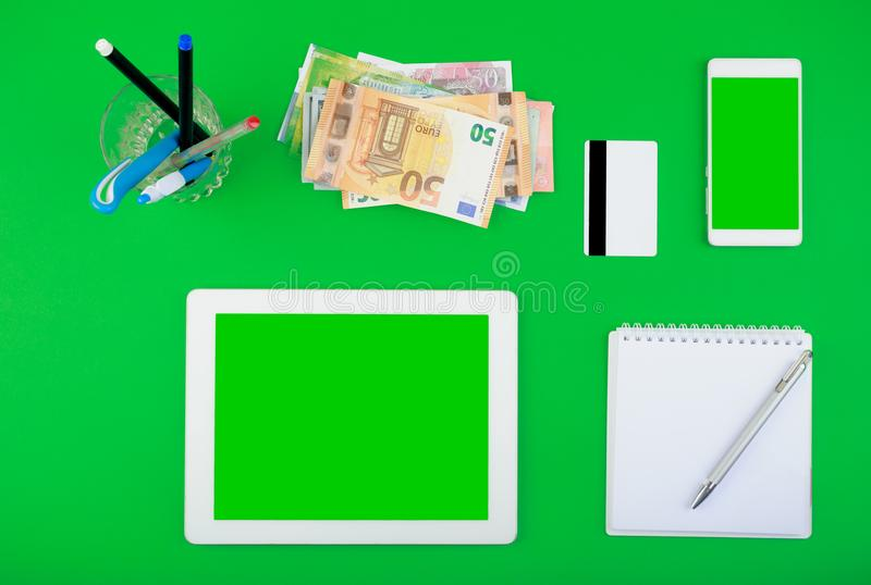 Draufsicht Worktop weiße Tablette und Smartphone mit einem leeren Bildschirm, Geld, Kreditkarte, Notizblock mit Stift und Stiftor lizenzfreies stockbild