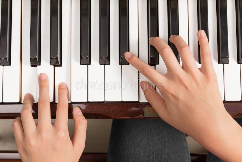 Draufsichtabschluß oben von den weiblichen Händen, die Klavier spielen stockbilder