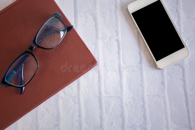 Draufsichtbürogeschäftstabelle Smartphonegläser des Arbeitsplatzes reservieren, Konzept: Konzept: kreative Arbeitstechnologie mod lizenzfreie stockfotos
