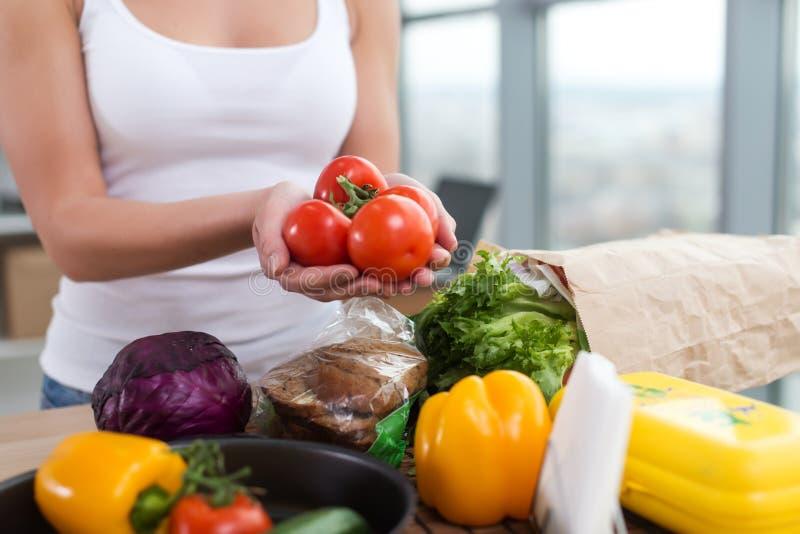 Draufsichtbild der Nahaufnahme von den weiblichen Händen, die frische saftige rote Tomaten über dem Küchentisch zeigen, bereiten  stockbilder