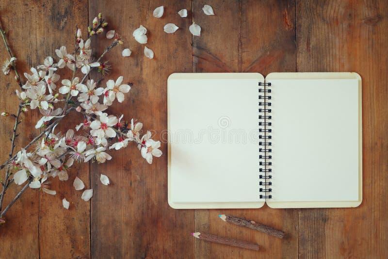 Draufsichtbild des Blüten-Baums des Frühlinges des weißen Kirschoffenen leeren Notizbuches als Nächstes auf Holztisch gefiltertes stockfotografie