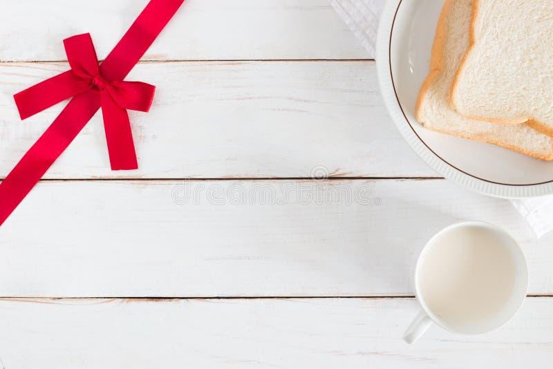 Draufsichtbild des geschnittenen Brotes auf Teller mit heißer Milch in der weißen Schale und Ecke haben Band auf weißem hölzernem stockbilder