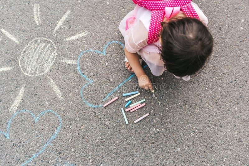 Draufsichtbild des glücklichen kleinen Mädchens trägt rosa Kleider- und Rucksackzeichnung mit bunten Kreiden auf dem Bürgersteig  stockbild
