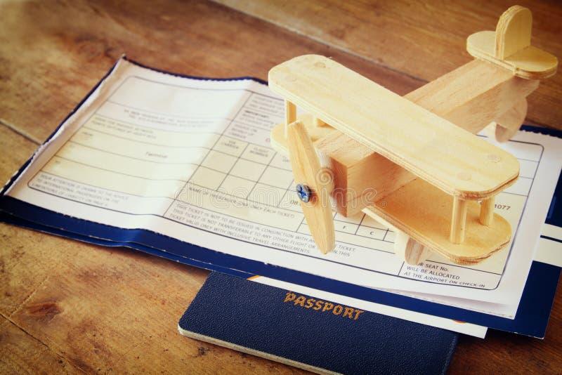 Draufsichtbild des hölzernen Flugzeuges und des Passes der Fliegenkarte über Holztisch stockbilder
