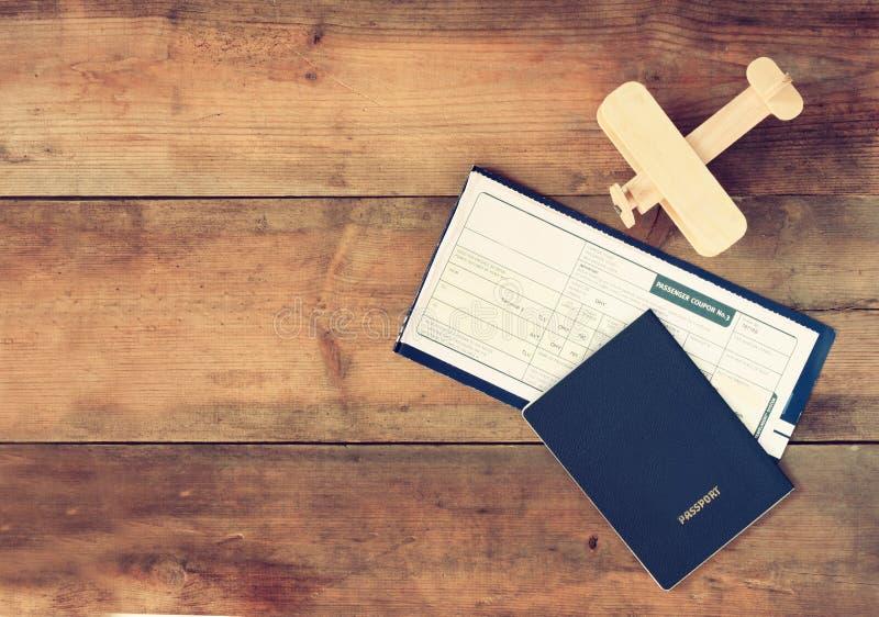 Draufsichtbild des hölzernen Flugzeuges und des Passes der Fliegenkarte über Holztisch stockfotografie