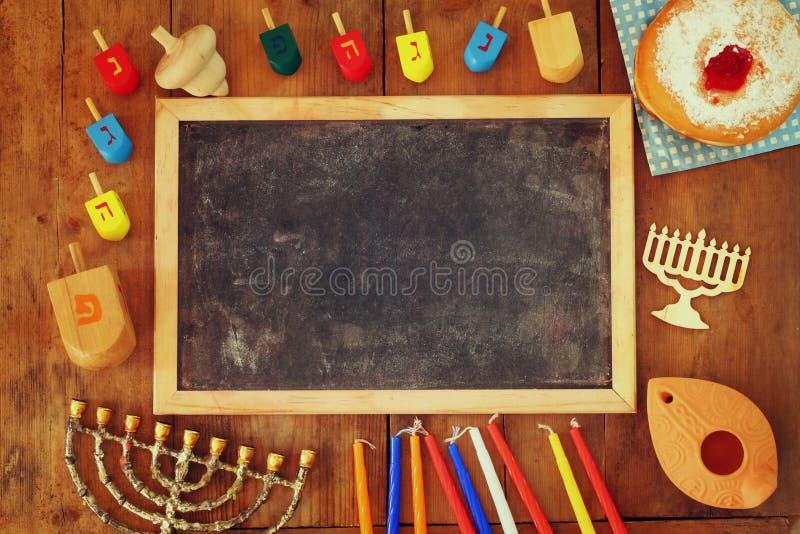 Draufsichtbild des jüdischen Feiertags Chanukka mit menorah (traditionelle Kandelaber), Schaumgummiringen und hölzernen dreidels  stockbild