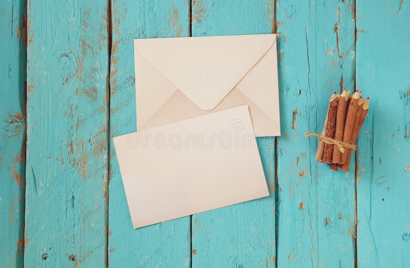 Draufsichtbild des leeren Briefpapiers und des Umschlags nahe bei bunten Bleistiften auf Holztisch Weinlese gefiltert und getont stockfotografie