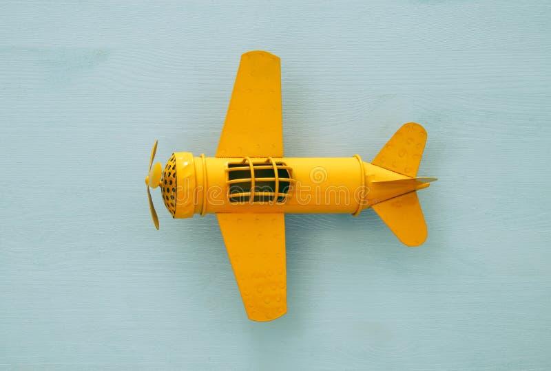 Draufsichtbild des Retro- gelbes Metallspielzeugflugzeuges über blauem Hintergrund stockfoto