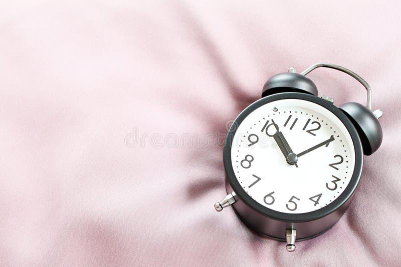 Draufsichtbild des schwarzen Retro- Weckers auf Bett am Morgen, bereiten für das Hinzufügen vor oder verspotten oben lizenzfreie stockfotografie