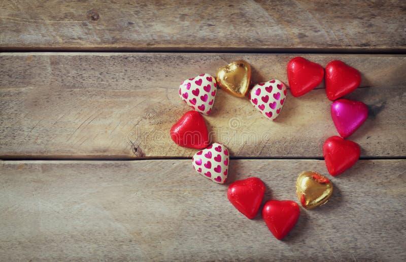 Draufsichtbild von bunten Herzformschokoladen auf Holztisch Valentinstagfeierkonzept stockbild