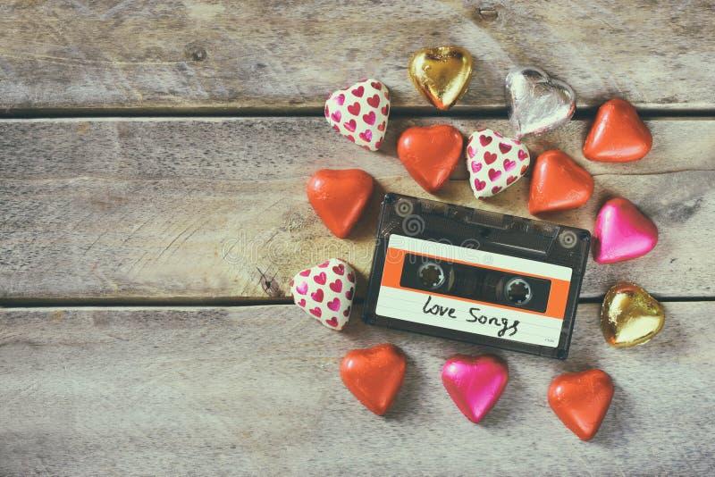 Draufsichtbild von bunten Herzformschokoladen und von Audiokassette auf Holztisch Valentinstagfeierkonzept lizenzfreie stockfotografie