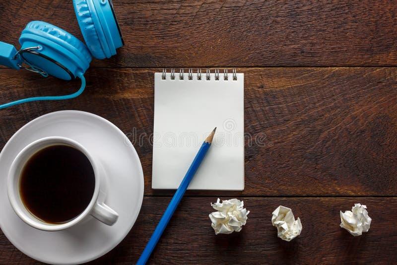 Draufsichtbleistift, Briefpapier, zerknitterte schwarzen Papierkaffee, Kopfhörer stockfotos