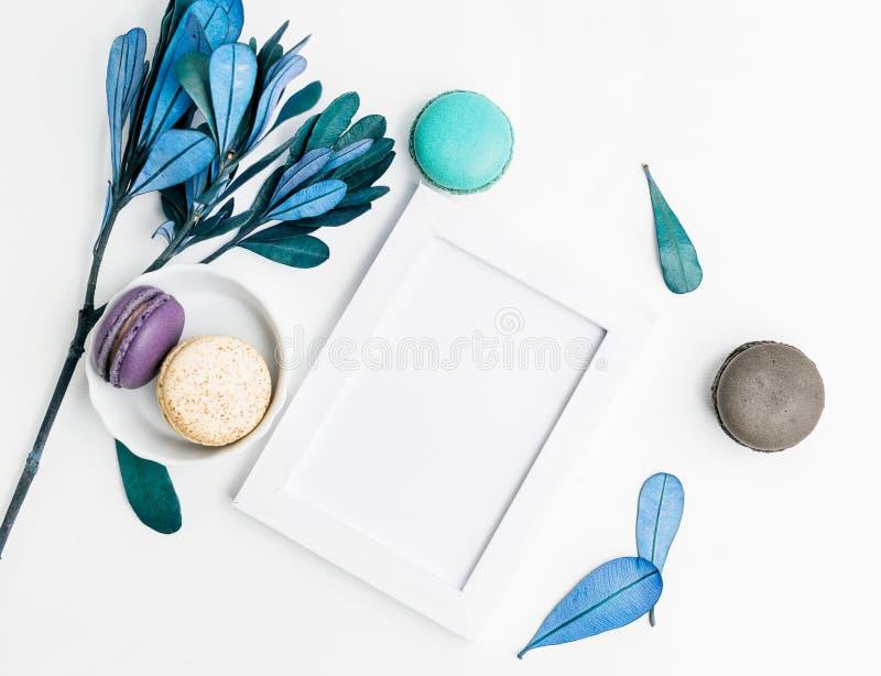 Draufsichtebene legen leeres Fotorahmenmodell mit macarons und Blaublättern stockbilder