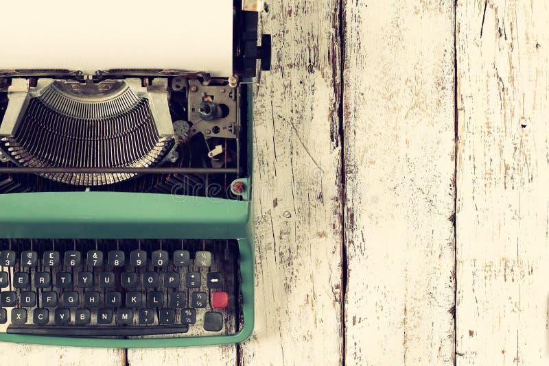 Draufsichtfoto der Weinleseschreibmaschine mit Leerseite, auf Holztisch Retro- gefiltertes Bild stockfoto