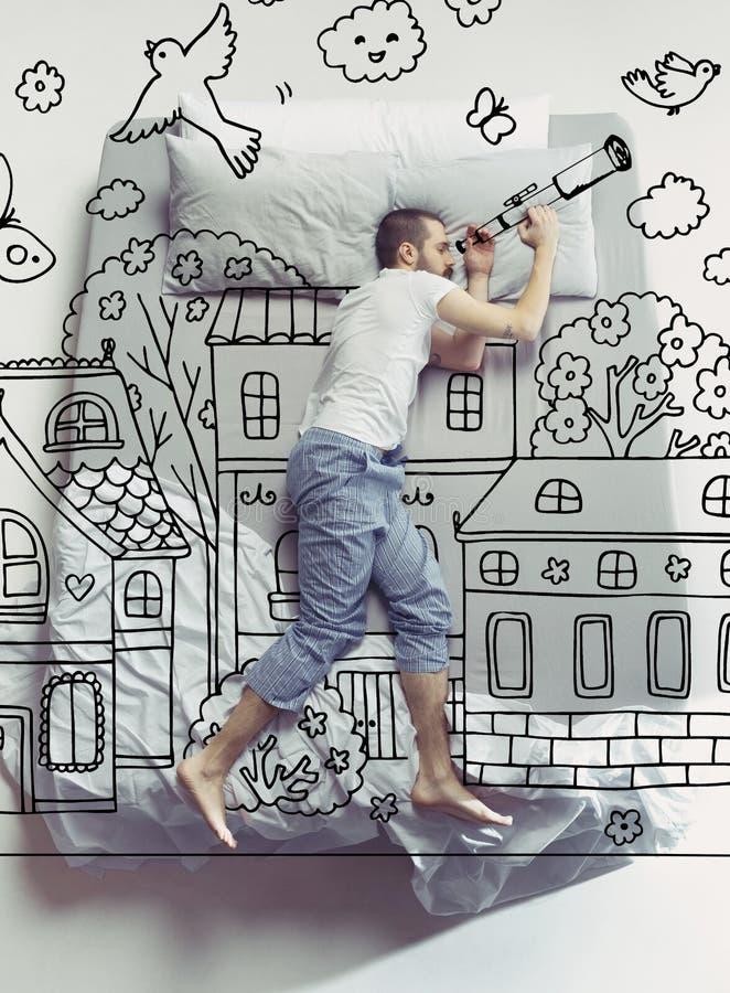Draufsichtfoto des jungen Mannes schlafend in einem großen weißen Bett und in seinen Träumen lizenzfreie stockbilder